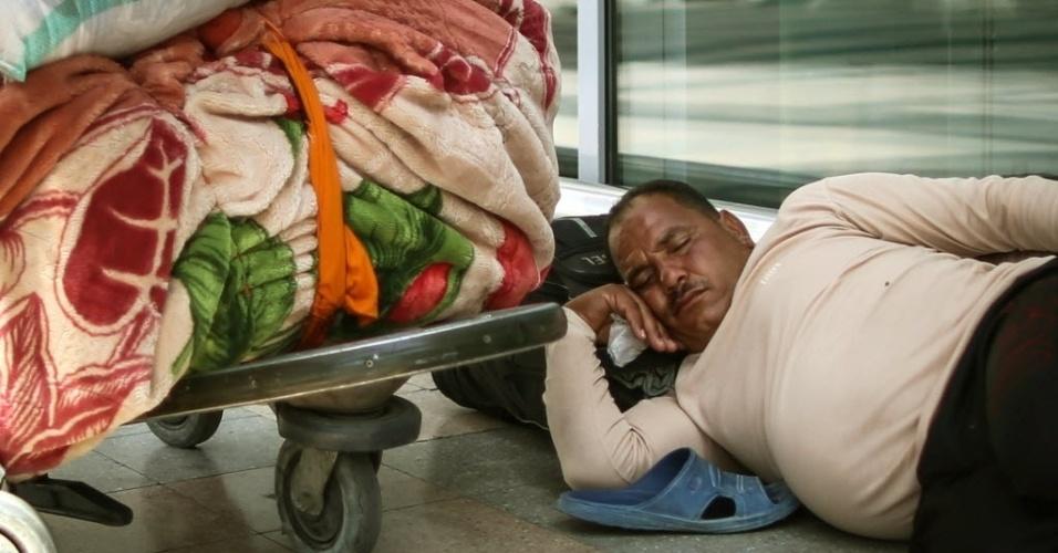 5.ago.2014 - Egípcio descansa no chão do Aeroporto Internacional do Cairo, depois de chegar da Tunísia, nesta terça-feira (5). Milhares de egípcios têm saído da Líbia através de helicópteros depois que a Tunísia fechou sua fronteira terrestre. Desde meados de julho eclodiram confrontos mortais entre milícias rivais em Trípoli e na cidade oriental de Benghazi