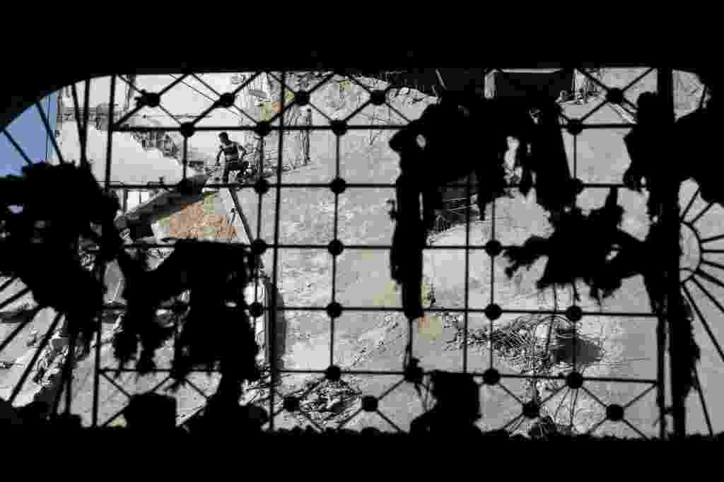 """6.jul.2014 - Homem palestino é visto através da janela de um edifício danificado por bombardeios durante a ofensiva de Israel, no bairro de Shejaia, na Cidade de Gaza, nesta quarta-feira (6). Israel e o movimento palestino Hamas, que controla a Faixa de Gaza, aceitaram um cessar-fogo de 72 horas, que entrou em vigor na terça-feira (5) às 8h (2h no horário de Brasília). Uma autoridade informou à agência AFP que Israel estaria """"pronto"""" para prorrogar o atual cessar-fogo na Faixa de Gaza sem condições e sem limite de tempo - Finbarr O'Reilly/ Reuters"""