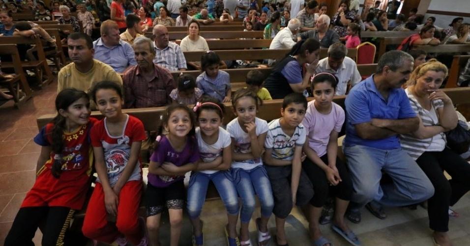 7.ago.2014 - Cristãos iraquianos, que fugiram da violência na aldeia de Qaraqosh, descansam na igreja Saint-Joseph, na cidade curda de Arbil, no Curdistão. Militantes do Estado Islâmico ampliaram as conquistas no norte do país, tomando mais cidades e fortalecendo sua posição próximo à região curda, em uma ofensiva que tem preocupado o governo de Bagdá e potências regionais
