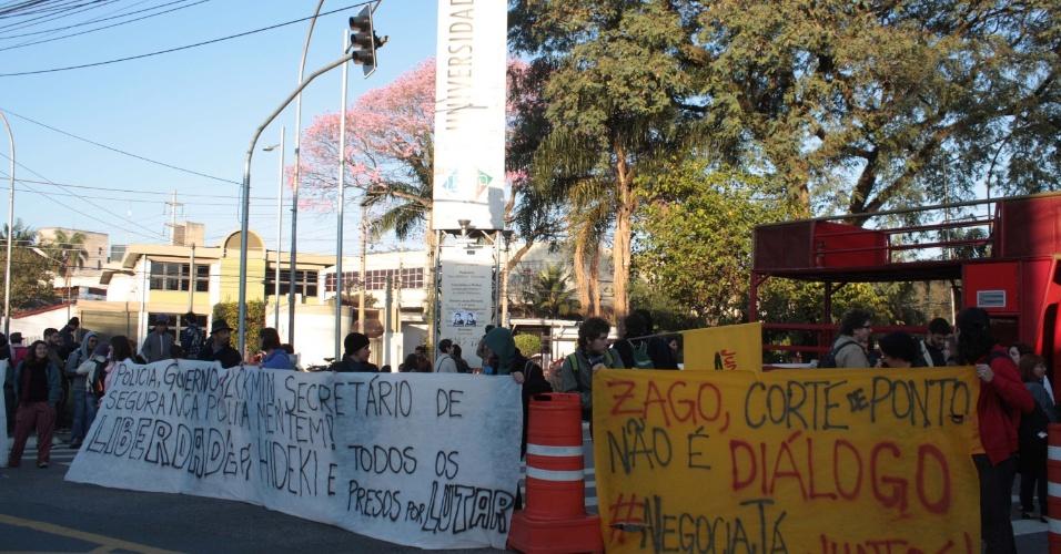 7.ago.2014 - Estudantes e funcionários da USP (Universidade de São Paulo) fecham os portões do campus na Rua Alvarenga em São Paulo, SP, na manhã desta quinta-feira (7), em protesto contra o corte dos salários de milhares de trabalhadores por exercerem o direito constitucional de greve. Os manifestantes também pedem a libertação do aluno e funcionário da USP Fábio Hideki Harano, que foi preso em uma manifestação na capital