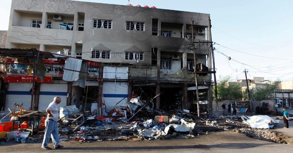 7.ago.2014 - Homem passa por local onde carro-bomba explodiu nesta quarta-feira (6) em Bagdá, capital iraquiana