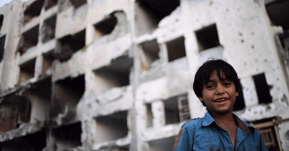 7.ago.2014 - Menino palestino sorri próximo a um edifício destruído nesta quinta-feira (7), em Beit Lahiya, no norte da faixa de Gaza. O Hamas fez sua primeira manifestação pública nesta quinta desde o cessar-fogo com Israel, afirmando que o grupo militante nunca desistirá de suas armas e que continuará lutando até que o bloqueio da faixa de Gaza seja levantado