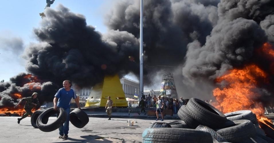 7.ago.2014 - Homem segura pneus durante um protesto na praça da Independência, em Kiev, na Ucrânia. Forças de segurança ucranianas tentaram remover um acampamento de manifestantes no centro da capital e entraram em conflito com os ocupantes