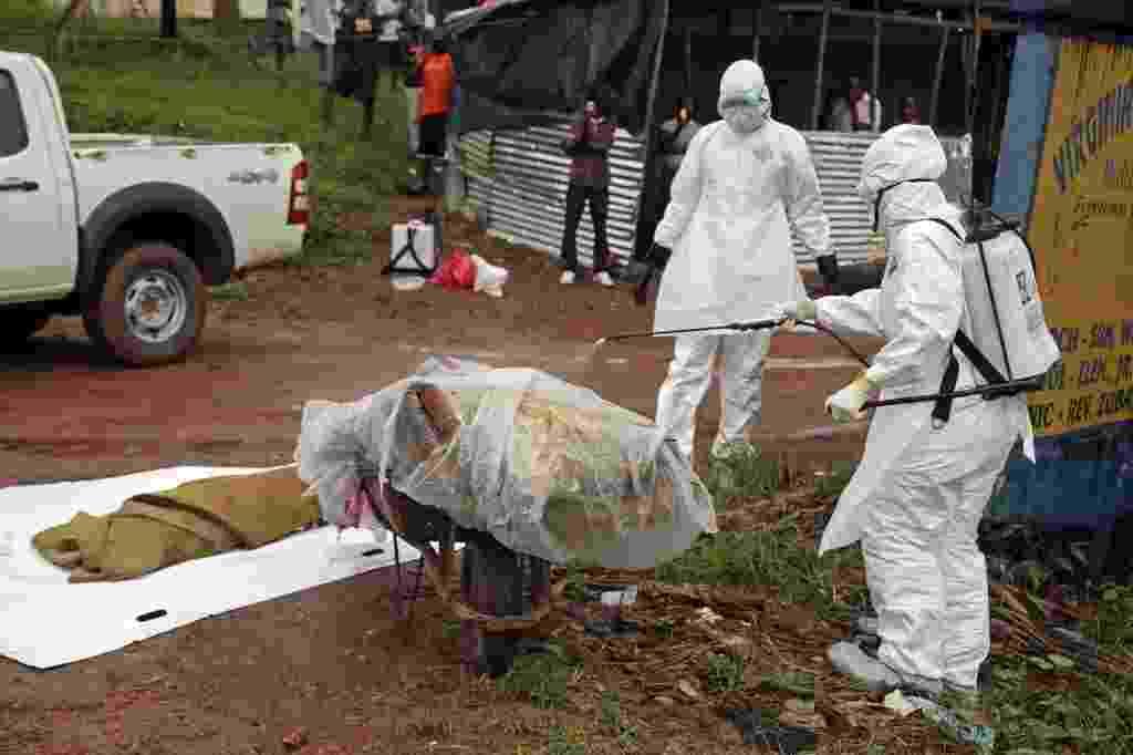 8.ago.2014 - Equipes de saúde desinfetam corpo e pertences de vítima do ebola em rua de Virginia, nos arredores de Monróvia, capital da Libéria - Ahmed Jallanzo/EPA/EFE