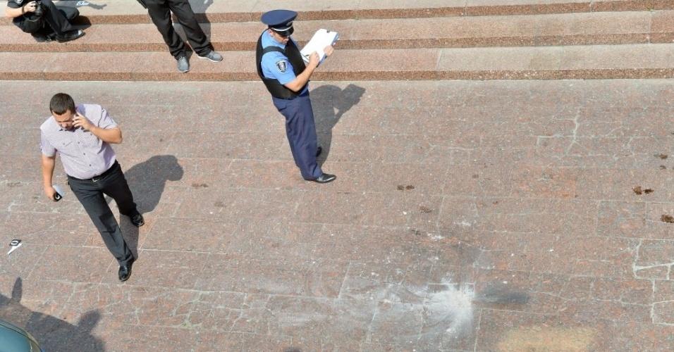 8.ago.2014 - Policiais inspecionam local onde ocorreu a explosão de uma granada perto da sede do governo ucraniano em Kiev. Duas pessoas ficaram feridas. O homem que lançou a granada foi preso com a ajuda de testemunhas do crime