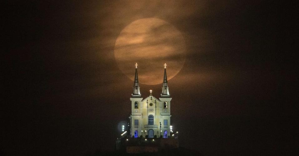 10.ago.2014 - A lua cheia surge atrás da Igreja de Nossa Senhora da Penha, no Rio de Janeiro, na noite do fenômeno da superlua