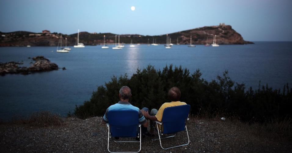 10.ago.2014 - Casal observa lua no céu de Sounio, próximo de Athenas, na Grécia. O fenômeno é chamado de ''lua perigeu'' pelos cientistas e ocorre quando a Lua está perto do horizonte e parece maior e mais brilhante do que as outras luas cheias.