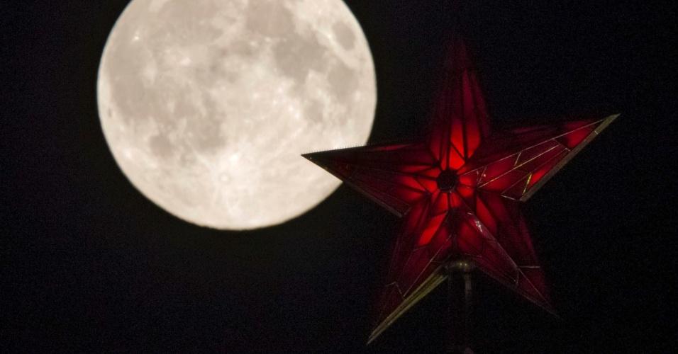 10.ago.2014 - Luz de superlua brilha mais do que a estrela da torre do Kremlin de Moscou, em Moscou, na Rússia. O fenômeno ocorre quando a Lua cheia coincide com o momento em que ela está mais próxima da Terra. Esta é a maior superlua do ano