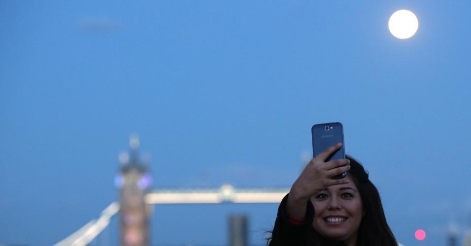 10.ago.2014 - Mulher faz selfie com superlua próximo a Tower Bridge, em Londres, Inglaterra. O fenômeno corre quando a Lua cheia coincide com o momento em que ela está mais próxima da Terra. Esta é a maior superlua do ano