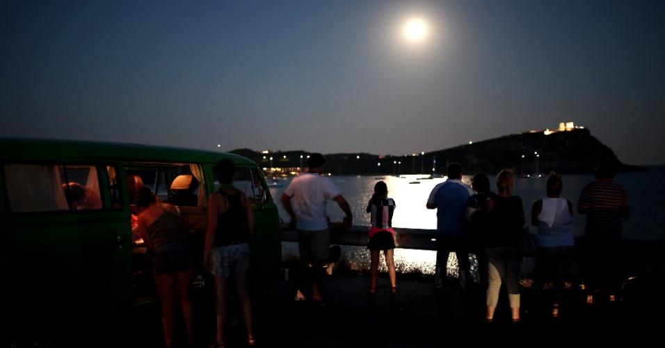 10.ago.2014 - Pessoas observam superlua no céu de Sounio, próximo de Athenas, na Grécia. O fenômeno é chamado de ''lua perigeu'' pelos cientistas e ocorre quando a Lua está perto do horizonte e parece maior e mais brilhante do que as outras luas cheias.