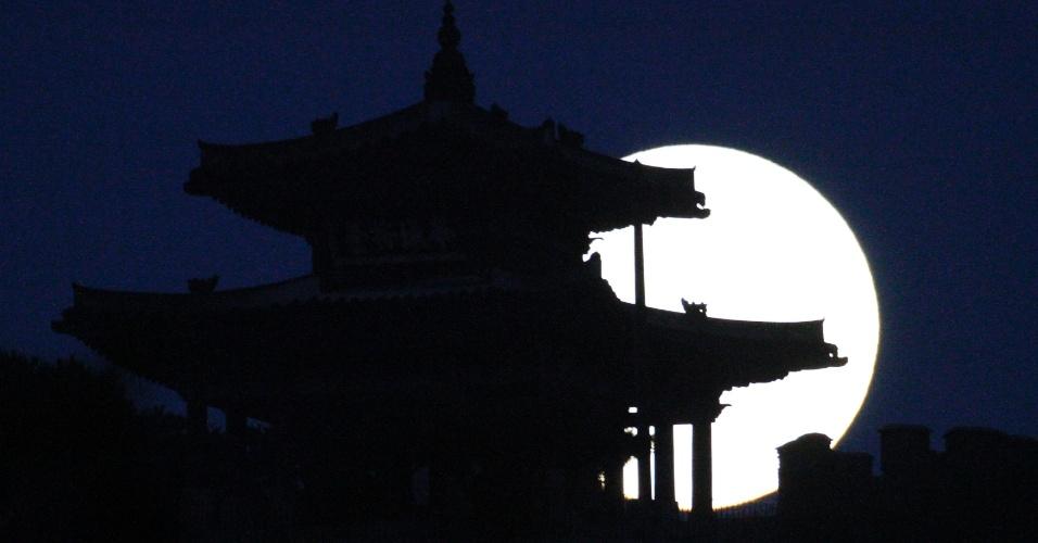 10.ago.2014 - Superlua nasce atrás da fortaleza Hwaseong, em Suwon, Coreia do Sul. O fenômeno corre quando a Lua cheia coincide com o momento em que ela está mais próxima da Terra. Esta é a maior superlua do ano