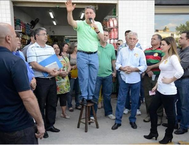 11.ago.2014 - O candidato ao governo do Rio de Janeiro Anthony Garotinho (PR) sobre em um banco para falar com moradores de Cordeiro, na região serrana do Rio de Janeiro, nesta segunda-feira (11). Garotinho fez uma caminhada no centro da cidade