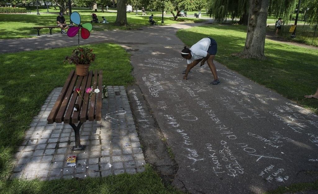 12.ago.2014 - Mulher escreve uma mensagem com giz no chão, em frente ao banco dos jardins públicos de Boston, onde uma cena do filme 'Gênio Indomável' (1997), estrelado pelos atores americanos Matt Damon e Robin Williams, foi filmada, nesta terça-feira (12). Robin Williams morreu nesta segunda-feira (11), aos 63 anos de idade. De acordo as autoridades locais, o corpo dele foi encontrado em sua casa, em Tiburon, na Califórnia, sem sinais vitais. A suspeita é de que a morte tenha sido causada por asfixia