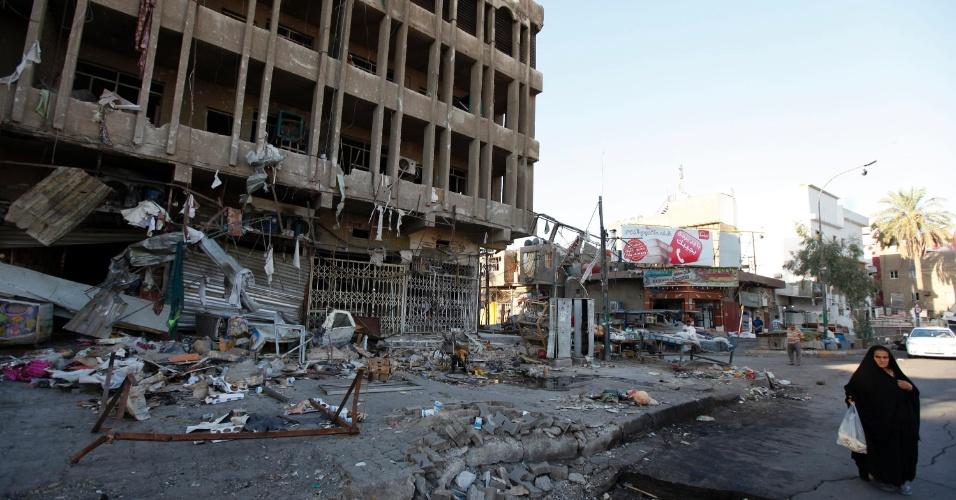 13.ago.2014 - Mulher caminha em frente a prédio destruído pela explosão de um carro-bomba durante ataque suicida em Bagdá, no Iraque