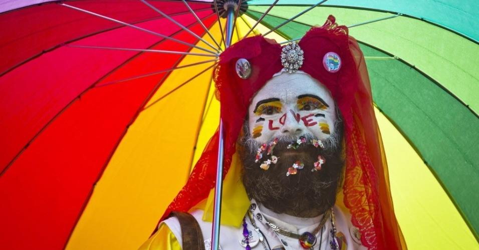 16.ago.2014 - Homem com guarda-chuva de arco-íris sorri durante a Parada Gay de Praga, na República Tcheca, neste sábado (16); o evento durou a semana toda e será encerrado no domingo (17)