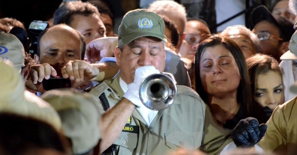 17.ago.2014 - Bombeiro toca marcha fúnebre antes de o caixão que carrega o corpo de Eduardo Campos ser enterrado ao lado dos restos mortais de Miguel Arraes, ex-governador de Pernambuco e avô de Campos, na noite deste domingo (17)