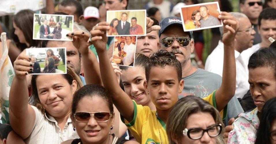 17.ago.2014 - Pessoas mostram fotos suas ou de familiares junto de Eduardo Campos, que será enterrado ainda neste domingo (17), em Recife (PE). Campos era candidato à presidência e morreu em um acidente de avião na última quarta-feira