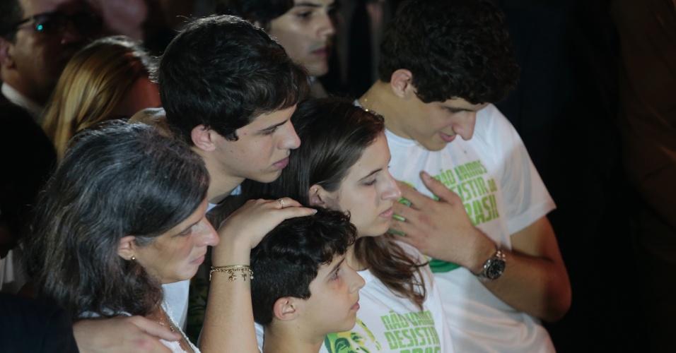 17.ago.2014 - Renata Campos e os filhos se abraçam enquanto o caixão com o corpo do ex-governador de Pernambuco, Eduardo Campos, é enterrado no cemitério de Santo Amaro, no Recife (PE), neste domingo (17)