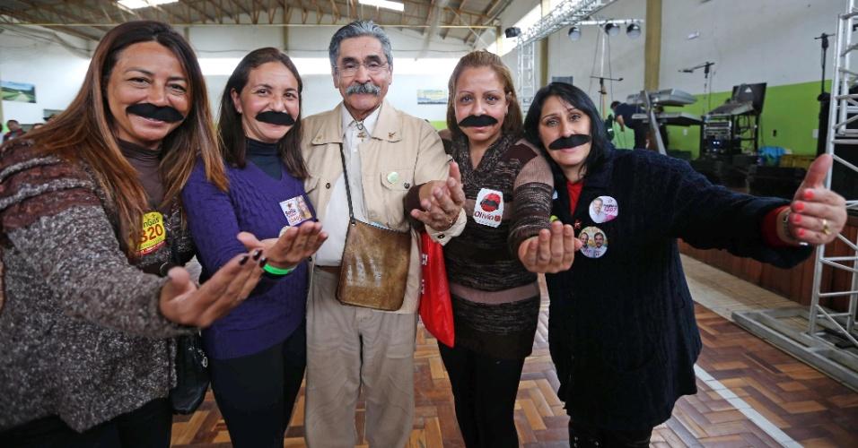 18.ago.2014 - Eleitoras usam falso bigode  em apoio a Olívio Dutra, candidato ao Senado pelo Partido dos Trabalhadores, que faz caminhada no bairro da Lomba do Pinheiro, em Porto Alegre, nesta segunda-feira (18)