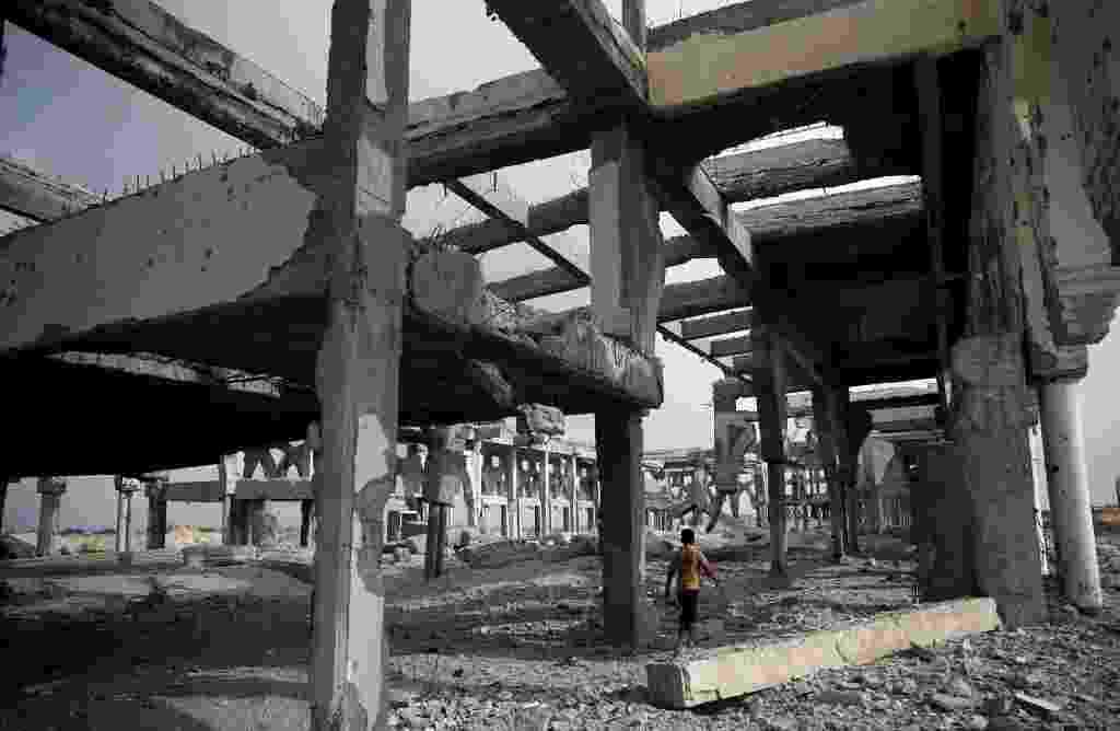 18.ago.2014 - Menino palestino caminha por escombros do terminal destruído do aeroporto internacional de Gaza, no sul da cidade de Rafah. Egípcias estão mediando as negociações indiretas entre Israel e os palestinos durante uma pausa de cinco dias no combate que deve expirar à meia-noite do horário local. Os palestinos rejeitaram qualquer proposta para desarmar Gaza e estão pressionando para que Israel suspenda seu bloqueio de oito anos no território costeiro, e também querem a criação de um porto marítimo e um aeroporto - Thomas Coex/AFP