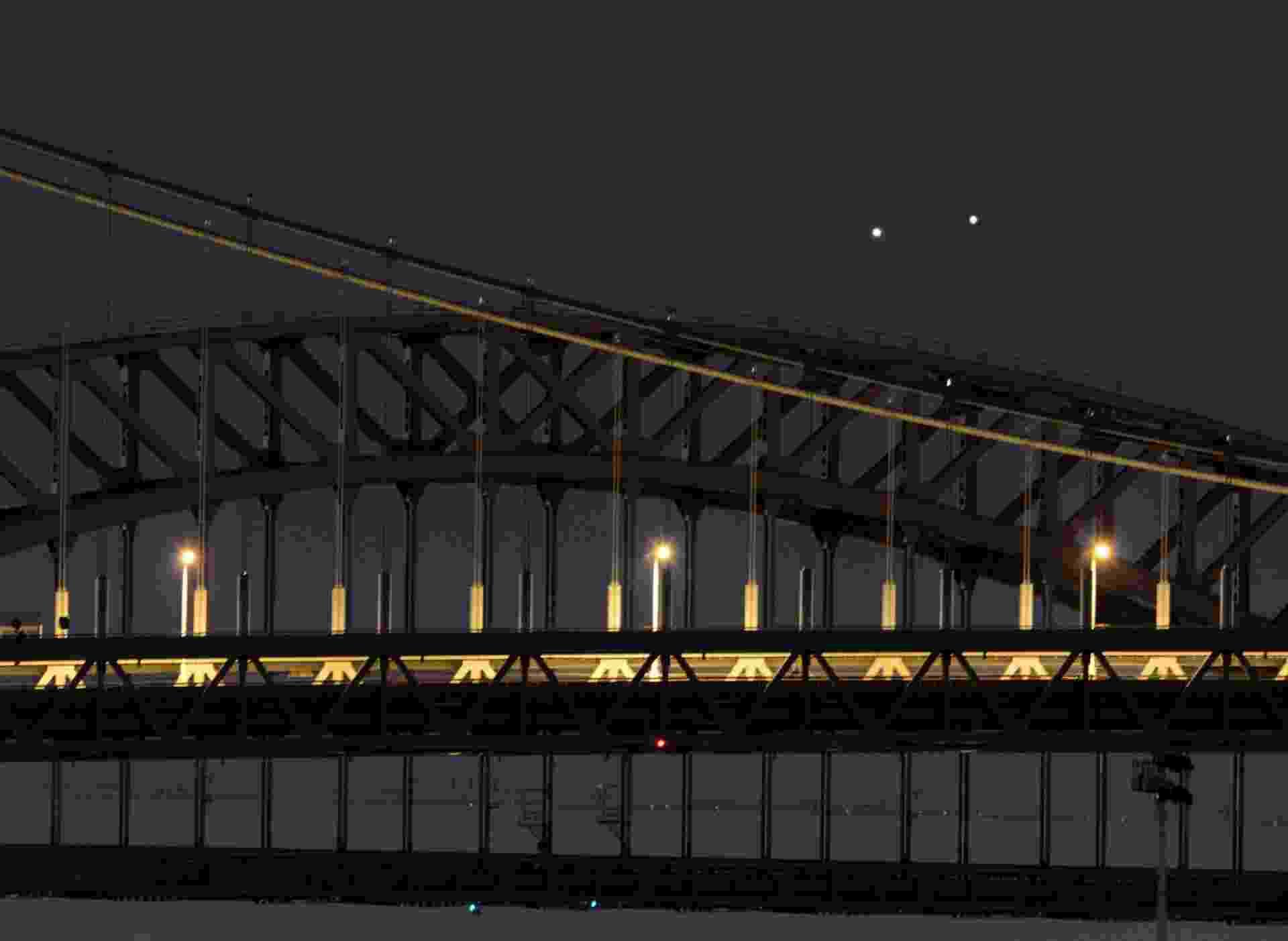 Vênus (esq.) e Júpiter (dir.) surgem muito próximos em uma rara conjunção sobre as pontes Hell Gate e Robert F. Kennedy na manhã desta segunda-feira (18) em Nova York, nos Estados Unidos - Stan Honda/AFP
