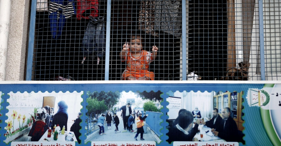 19.ago.2014 - Criança refugiada palestina observa o movimento atrás em escola da ONU em Jabalia que recebeu moradores da fixa de Gaza fugindo da operação de Israel no território. Negociadores israelenses e palestinos no Cairo (Egito) enfrentam um novo prazo para acabar com o derramamento de sangue na faixa de Gaza, depois de estender o cessar-fogo vigente por mais 24 horas