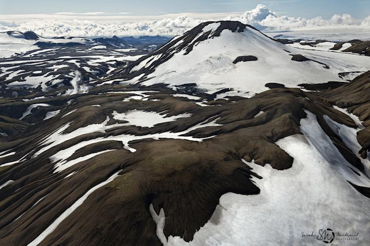 19.ago.2014 - Conhecida também como a 'terra do gelo', a Islândia combina paisagens como essa, com montanhas cobertas de neve, a outras em que rios cortam uma região árida ou um vale verde. A imagem faz parte da série da fotógrafa Sarah Martinet, que fez suas fotos a partir de um pequeno avião