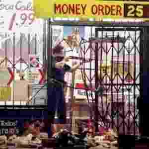 19.ago.2014 - Nesta foto do dia 30 de abril de 1992, um policial de Los Angeles aponta arma para um saqueador em um mercado em Los Angeles. A absolvição de quatro policiais brancos que haviam brutalmente espancado um taxista negro, Rodney King, em 3 de março de 1991, culminou em protestos no local. A violência se espalhou para São Francisco, Las Vegas, Atlanta e Nova York, deixando 59 mortos e 2.328 feridos - John Gaps 3º/AP