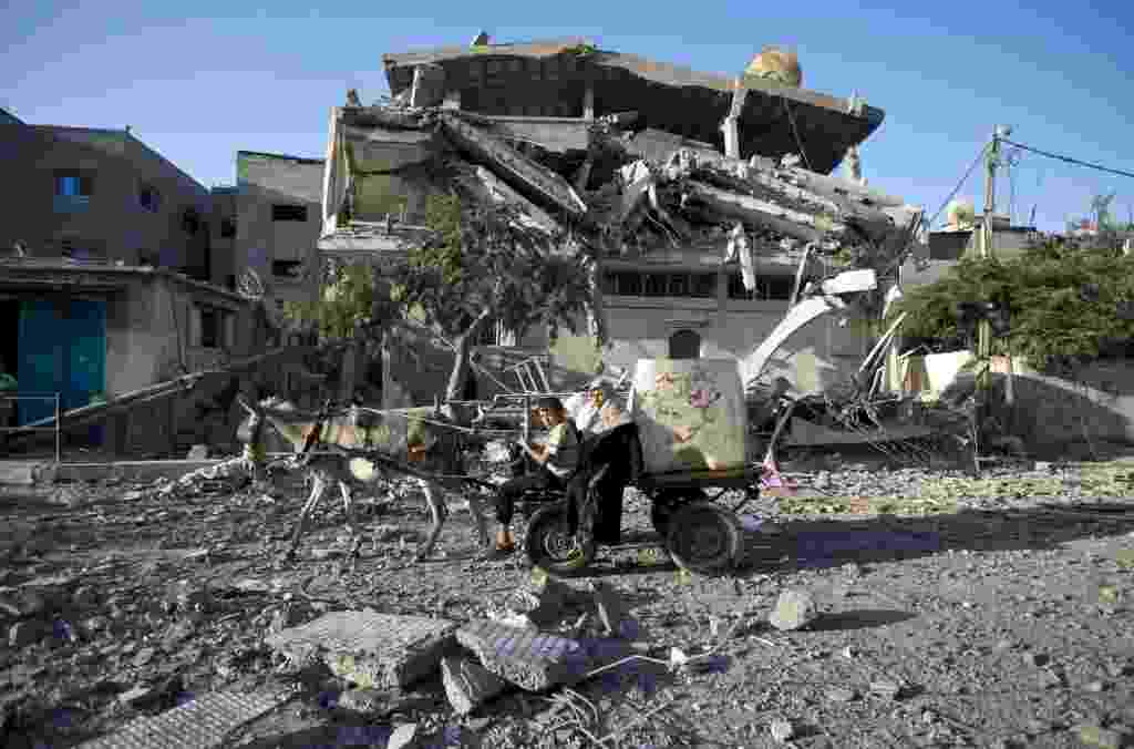 20.ago.2014 - Palestinos conduzem carroça perto de casa destruída durante os ataques aéreos israelenses no campo de refugiados de Jabalia, na faixa de Gaza. O Hamas disse que um ataque aéreo israelense matou a esposa e o filho de seu chefe militar de Gaza - Mahmud Hams/AFP