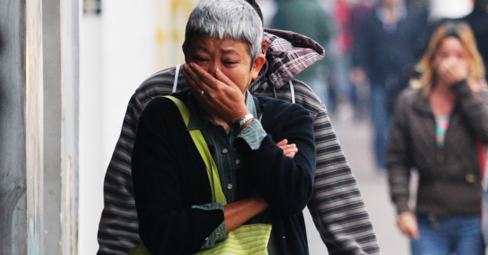 20.ago.2014 - Pedestre tenta se proteger contra o gás lacrimogêneo lançado pela PM contra os grevistas da USP na região da avenida Vital Brasil, zona oeste de São Paulo