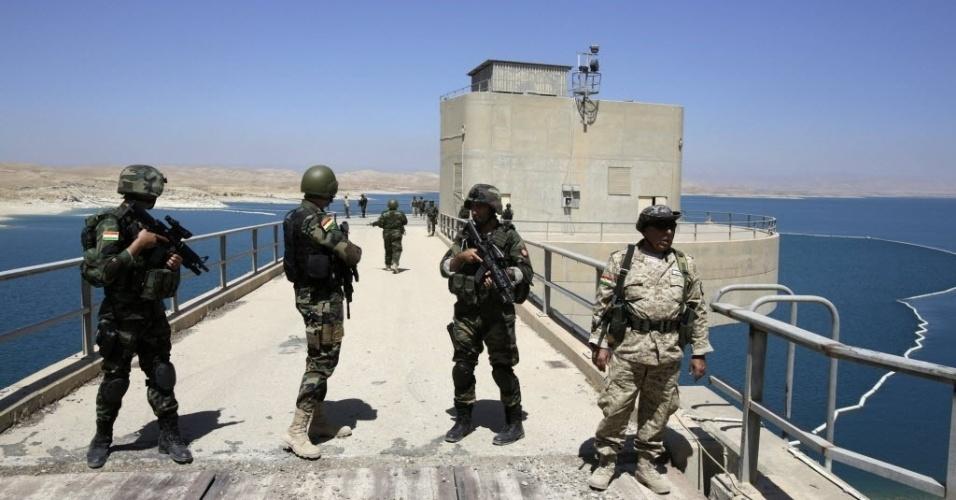 21.ago.2014 - Combatentes curdos patrulham área da represa de Mosul, no norte do Iraque. Apesar das falhas estruturais, a maior barragem do país com 3,6 km de extensão, construída por um consórcio alemão-italiano na década de 1980, é fonte vital de energia para Mosul, a maior cidade do norte do Iraque com  1,7 milhões de habitantes. Os insurgentes do Estado Islâmico havia tomado o controle da barragem nas últimas semanas. As forças iraquianas e curdas conseguiram retomar o controle do local com a ajuda de ataques aéreos dos EUA