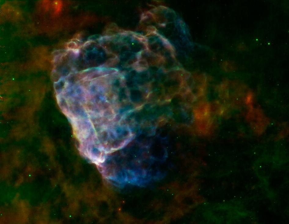 21.ago.2014 - Imagem feita a partir de uma supernova captada pela Nasa e pela Agência Espacial Europeia mostra nuvem de poeira colorida. Informação em infravermelho do fotômetro de imagem do telescópio Spitzer, da Nasa, em ondas de 24 e 70 microns surgem em vermelho e verde e raios X do XMM-Newton em um alcance de 0.3 a 8 kiloelectron volts em azul