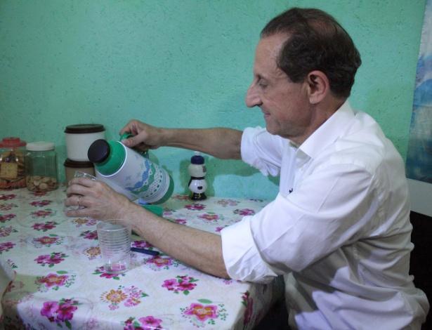 21.ago.2014 - O candidato ao governo de São Paulo pelo PMDB, Paulo Skaf, toma café na casa do pedreiro Fabio Machado da Conceição, durante caminhada de campanha no Jardim Ângela, na zona sul de São Paulo, nesta quinta-feira (21)
