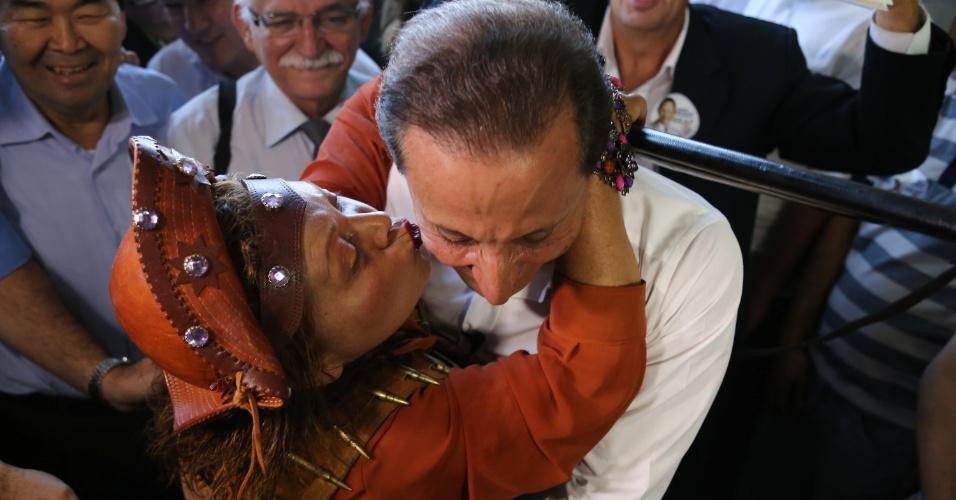 22.ago.2014 - Mulher com roupa de cangaceira beija o candidato ao governo do Estado de São Paulo pelo PMDB, Paulo Skaf, durante visita a comerciantes do mercadão da Lapa, na capital paulista. Skaf fez caminhada de campanha pelo mercadão e por outras ruas de comércio do bairro
