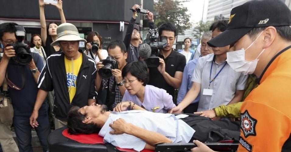 22.ago.2014 - O sul-coreano Kim Young-oh (à esquerda), que perdeu a filha de 16 anos no desastre da balsa Sewol em abril, é transportado para uma ambulância, em Seul. Ele passou mal e foi hospitalizado ao promover um jejum de 40 dias para reivindicar um inquérito independente sobre o acidente, que deixou mais de 300 mortos e desaparecidos