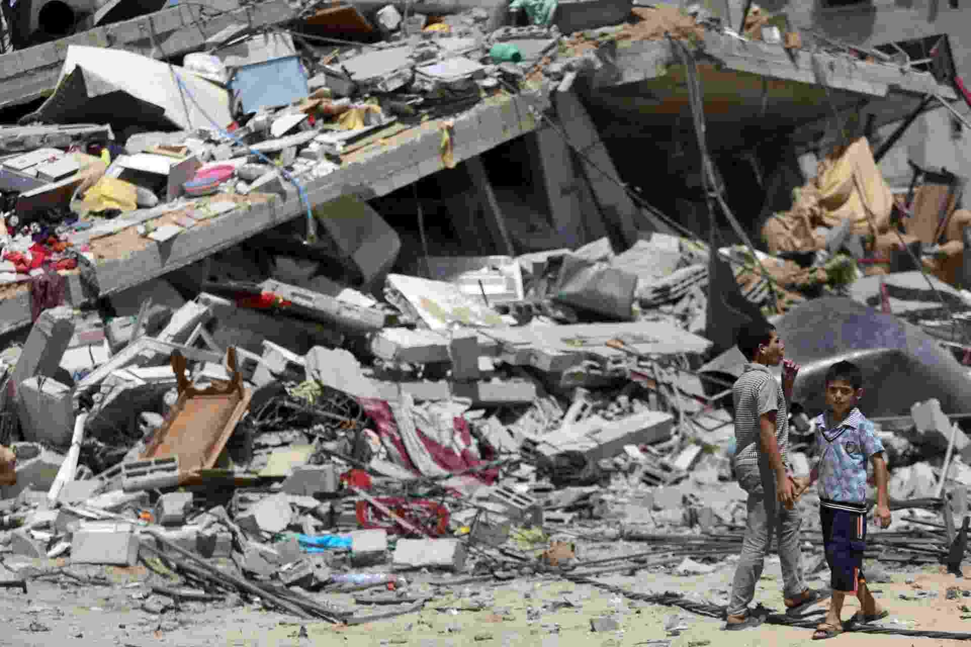 23.ago.2014 - Jovens palestinos andam sobre escombros de casa destruída ao sul da cidade de Gaza, após ataques aéreos israelenses bombardearem a região. O ataque matou cinco pessoas da mesma família, incluindo duas crianças, após o fracasso das negociações entre Israel e os palestinos e a retomada das hostilidades na terça-feira - Mohammed Saber/EPA/EFE