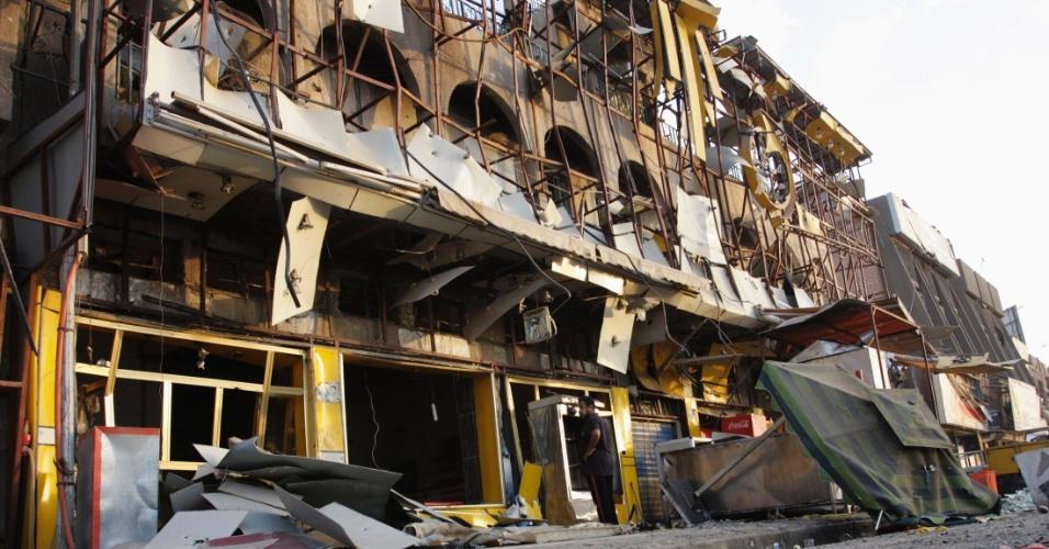 25.ago.2014 - Homem observa os destroços deixados por um atentado a bomba que matou sete pessoas no último domingo (24) em uma área predominantemente xiita de Bagdá. Um carro-bomba explodiu e destruiu a fachada de um edifício
