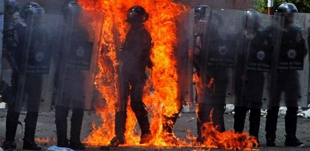 Policial fica em chamas após ser atingido por coquetel molotov jogado por manifestante durante proteso em San Cristobal, na Venezuela - George Castellanos/AFP