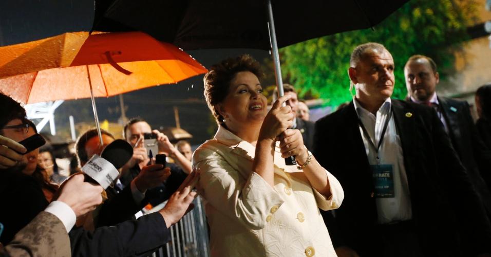 26.ago.2014 - A candidata à reeleição pelo PT, Dilma Rousseff, usa sombrinha para se proteger de chuva na noite desta sexta, ao chegar aos estúdios da TV Bandeirantes, em São Paulo, para participar do primeiro debate entre presidenciáveis das eleições de 2014