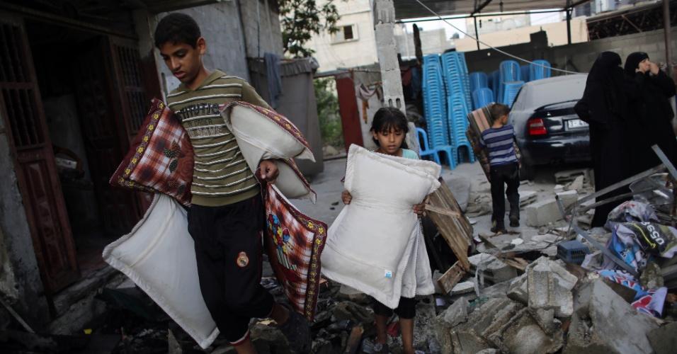 26.ago.2014 -  Crianças palestinas carregam alguns pertences após a realização de um bombardeio israelense na cidade de Rafah, no sul da faixa de Gaza, nesta terça-feira (26). O governo do Egito tenta, até agora sem sucesso, um acordo entre Israel e o Hamas por um novo cessar-fogo