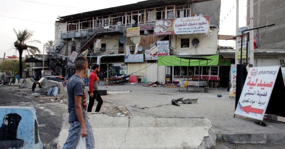 26.ago.2014 - Iraquianos passam diante do local da explosão de um carro-bomba em Bagdá. Na segunda-feira (25), dois carros-bomba mataram pelo menos 11 pessoas e feriram 25 em um bairro de maioria xiita da capital iraquiana. Um deles foi detonado em uma rua movimentada, e outro em frente a um restaurante, segundo a polícia. Outros ataques pela cidade causaram mais de 30 mortes