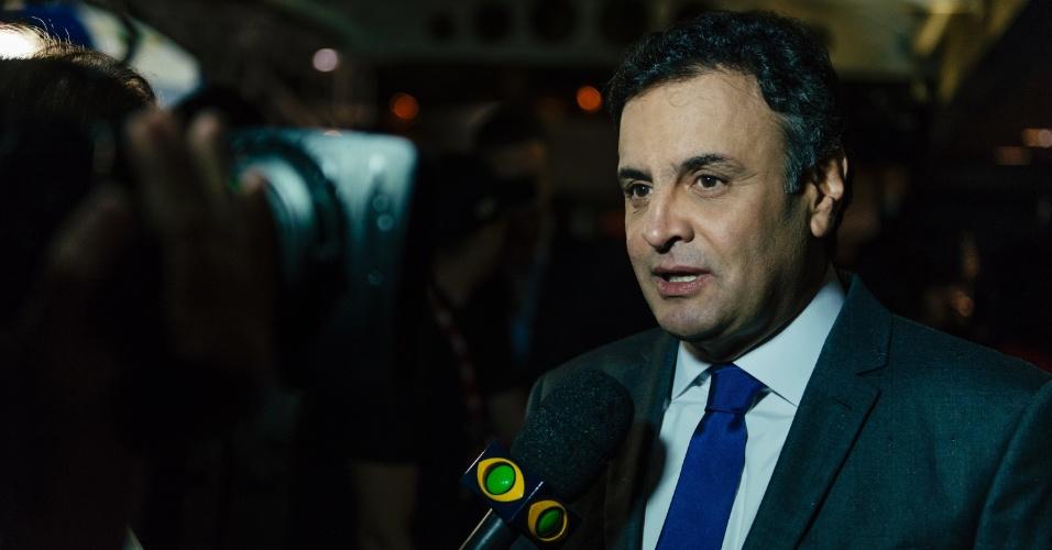 26.ago.2014 - O candidato Aécio Neves (PSDB) fala com jornalistas da Rede Bandeirantes antes do início do debate promovido pelo grupo em São Paulo, na noite desta terça