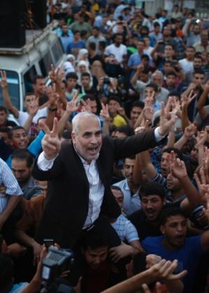 """O porta-voz do Hamas Fawzi Barhoum é carregado por palestinos durante celebração do que afirma ser """"uma vitória sobre Israel"""", após o anúncio do cessar-fogo na cidade de Gaza"""