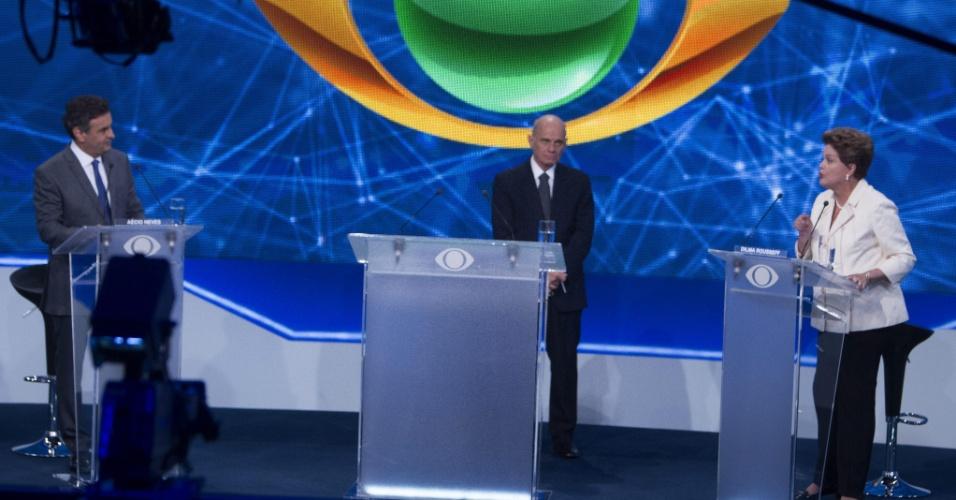 26.ago.2014 - Os candidatos Dilma Rousseff (PT, à direita), e Aécio Neves (PSDB, à esquerda) trocam questionamentos com a mediação do apresentador Ricardo Boechat (ao centro) durante o primeiro debate entre os concorrentes à Presidência, promovido pela TV Bandeirantes nesta terça-feira em São Paulo (SP)