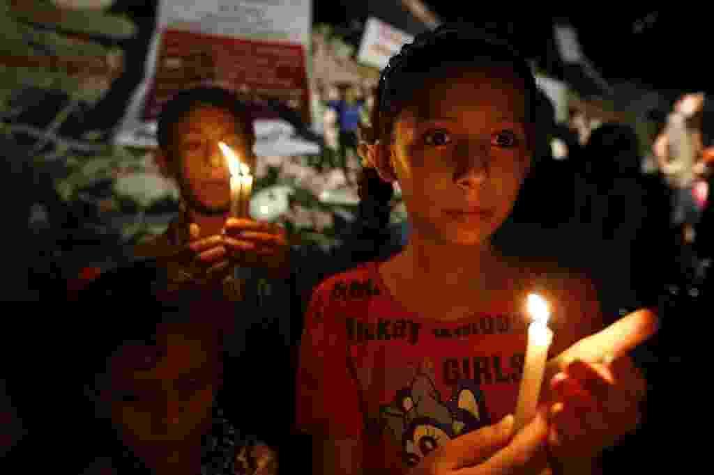 27.ago.2014 - Crianças palestinas carregam velas próximo a prédios destruídos por bombardeios de Israel na Faixa de Gaza, nesta quarta-feira - Mohammed Abed/AFP