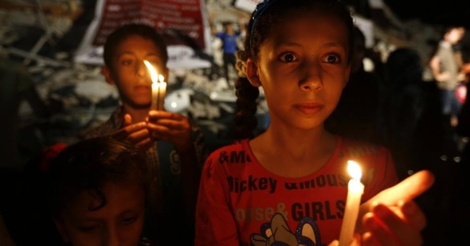 27.ago.2014 - Crianças palestinas carregam velas próximo a prédios destruídos por bombardeios de Israel na Faixa de Gaza, nesta quarta-feira
