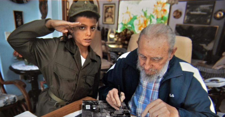 27.ago.2014 - Marlon Méndez, 8, faz saudação militar ao lado de Fidel Castro durante visita à casa do ex-ditador cubano, em Havana, no último dia 16 de agosto de 2014