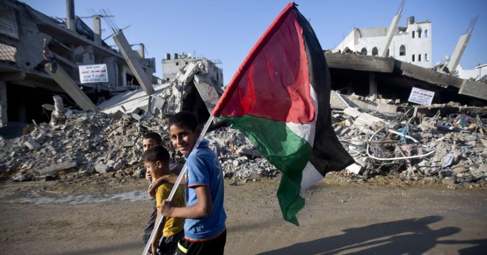 27.ago.2014 - Meninos palestinos carregam bandeira da nação enquanto passam em frente a casas destruídas no bairro de Shejaiya, na cidade de Gaza