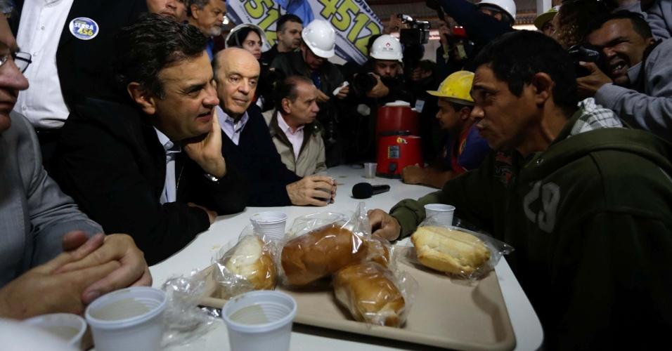 28.ago.2014 - O candidato à Presidência da República pelo PSDB, Aécio Neves, acompanhado do candidato ao Senado, José Serra, toma café da manhã com operários da construção civil em São Paulo (SP), nesta quinta-feira (28)