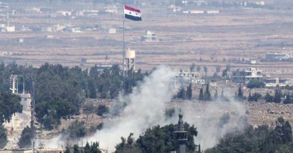 29.ago.2014 - Bandeira síria é içada nesta sexta-feira (29) na aldeia de Quneitra durante os combates entre as forças leais ao ditador sírio, Bashar Assad, e rebeldes, na fronteira com Israel. Rebeldes sírios, incluindo um braço da Al Qaeda, assumiram o controle das Colinas de Golã na quarta-feira